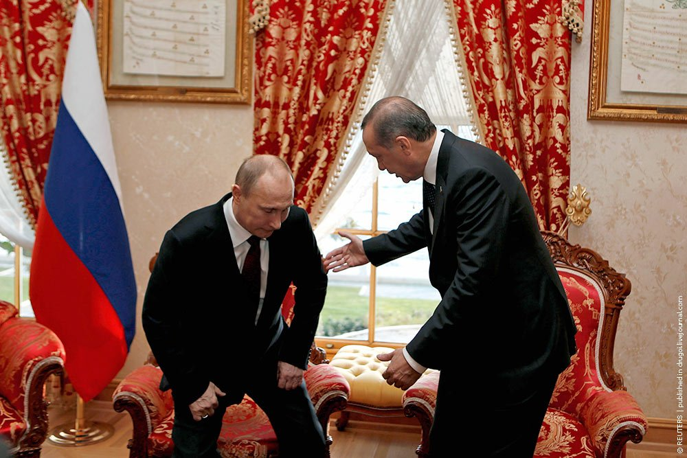 Turkey's Prime Minister Tayyip Erdogan gestures as Russia's President Vladimir Putin prepares to sit during their meeting in Istanbul